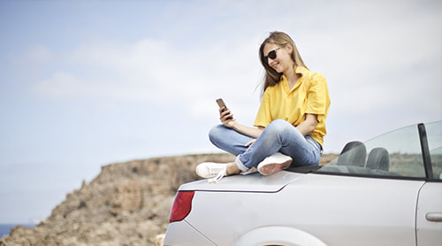 Girl texting on top of the car